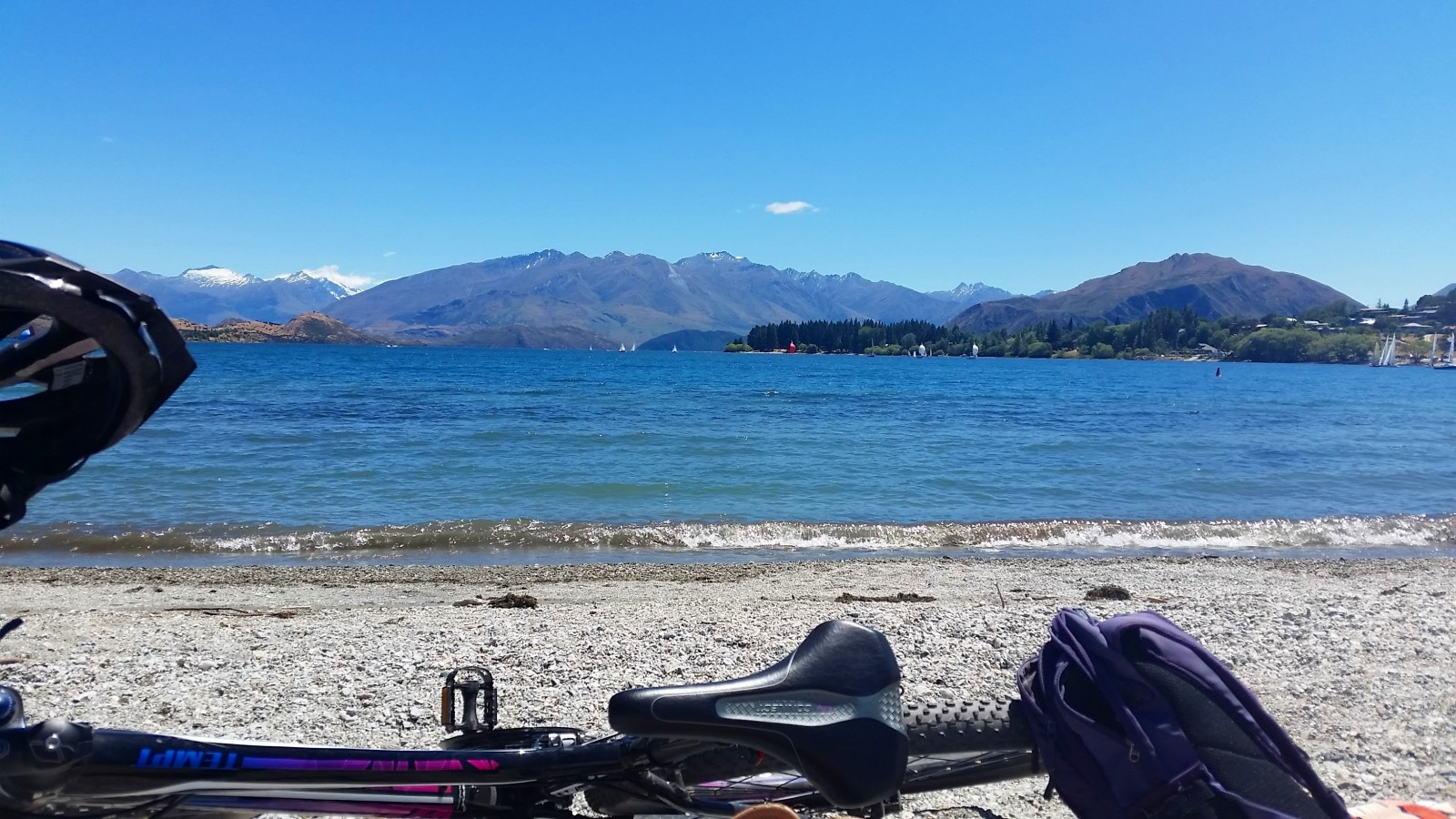 mountain biking along the lake side at Wanaka on a sunny day