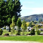 tents and caravans on grassy sites at Wanaka Lakeview holiday park with Mount Iron in the background